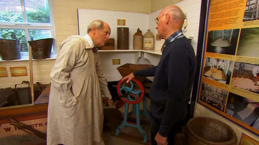 Charlie learns how to mill cheese in the Cheese Room at Nantwich Museum